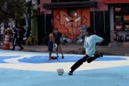 BRA01. SAO PAULO (BRASIL), 10/06/18. - Los niños juegan con pelota sobre una enorme bandera de Brasil, pintada sobre el asfalto. A cuatro días de comenzar la mayor fiesta mundial del fútbol, aficionados armados de brochas, pinturas, pitas, tijeras y papel ultiman detalles sobre algunas calles de São Paulo, que se visten de color para apoyar a su Canarinha, pese a la apatía que ronda este año a sus seguidores en Brasil. EFE/Marcelo Chello