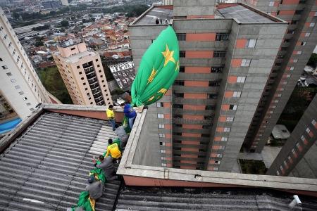 BRA50. SAO PAULO (BRASIL), 17/06/18. - Los residentes de un conjunto de edificios en Sao Paulo sacuden este domingo 17 de junio una bandera gigante de 63 metros de altura y 17 de ancho para conmemorar el juego de estrenos de la selección brasileña en la Copa del Mundo de Rusia. La bandera forma parte de una tradición que cumple 20 años. EFE/Marcelo Chello