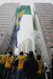 BRA51. SAO PAULO (BRASIL), 17/06/18. - Los residentes de un conjunto de edificios en Sao Paulo sacuden este domingo 17 de junio una bandera gigante de 63 metros de altura y 17 de ancho para conmemorar el juego de estrenos de la selección brasileña en la Copa del Mundo de Rusia. La bandera forma parte de una tradición que cumple 20 años. EFE/Marcelo Chello