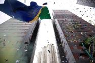 BRA52. SAO PAULO (BRASIL), 17/06/18. - Los residentes de un conjunto de edificios en Sao Paulo sacuden este domingo 17 de junio una bandera gigante de 63 metros de altura y 17 de ancho para conmemorar el juego de estrenos de la selección brasileña en la Copa del Mundo de Rusia. La bandera forma parte de una tradición que cumple 20 años. EFE/Marcelo Chello