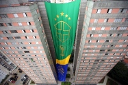 BRA56. SAO PAULO (BRASIL), 17/06/18. - Los residentes de un conjunto de edificios en Sao Paulo sacuden este domingo 17 de junio una bandera gigante de 63 metros de altura y 17 de ancho para conmemorar el juego de estrenos de la selección brasileña en la Copa del Mundo de Rusia. La bandera forma parte de una tradición que cumple 20 años. EFE/Marcelo Chello